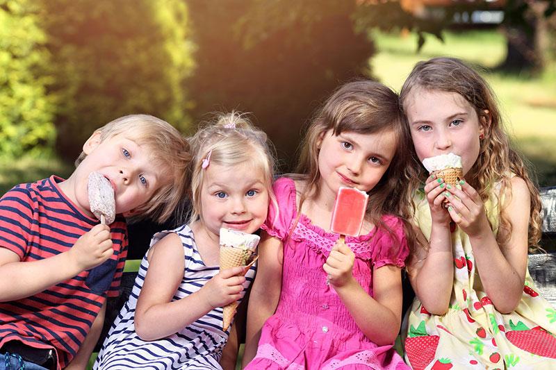 Kuvassa lapset syövät jäätelöä aurinkoisena kesäpäivänä