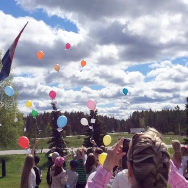 Kuvassa koululaiset lennättävät ilmapallot taivaalle